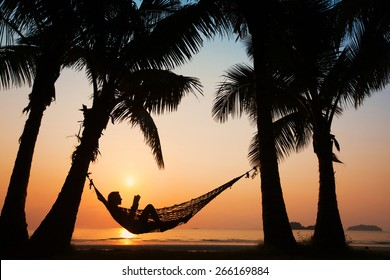 beach vacations, silhouette of woman reading in hammock