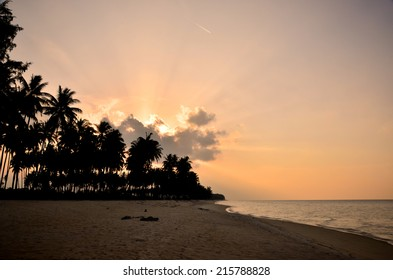 Beach view with cloudy, warm sky and sun rays.