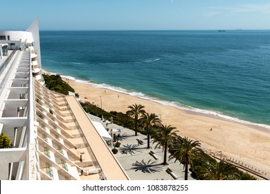 Beach view with palm trees from the hotel balcony in Sesimbra, Portugal