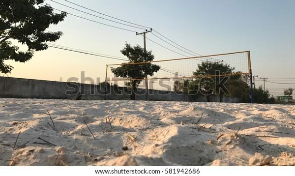 Beach volleyball court with sunlight.