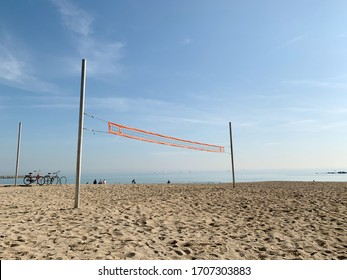 Beach volleyball net in an empty beach with yellow sand and blue sky.