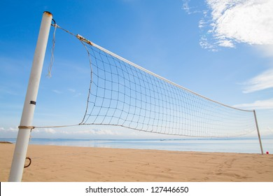 A beach volleyball net on the beach with a clear and sunny sky