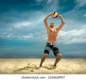 Beach volleyball player in action at sunny day under blue sky. Sport, holidays, athlete, free time concept.