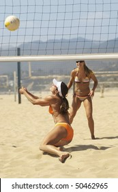 Beach volleyball player diving for volleyball near net