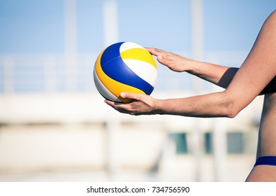 Beach volleyball player, playing summer. Woman with ball. A woman body holding a beach volley ball in hand.