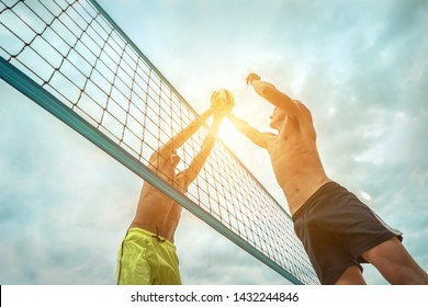 Beach Volleyball players in sunglasses in action with ball under sunlight. Popular Dynamic outdoor sport for people.