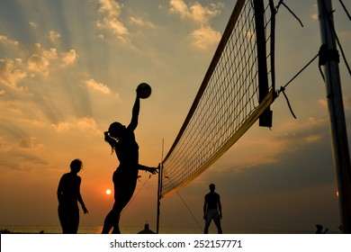 Beach volleyball silhouette at sunset , motion blurred