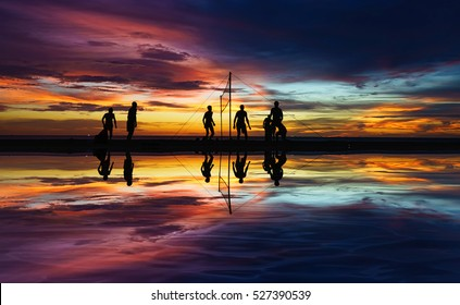 Beach volleyball silhouette at sunset with reflection in water.