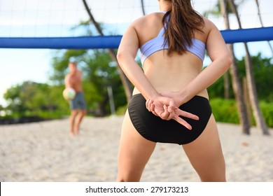 Beach volleyball woman player giving hand sign signal for play. Female athlete playing beach volley ball sport outdoors in summer in sports bikini. Healthy active lifestyle concept.