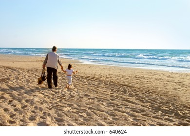 Beach walk - father walking on the beach with his daughter