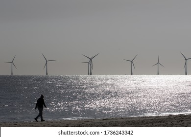 Beach walk. Morning coronavirus covid19 lockdown isolation exercise by alternative energy offshore wind farm turbines. Person walking alone along the UK coast at dawn. Healthy lifestyle.