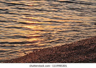 Beach water sun reflection at sunset colors