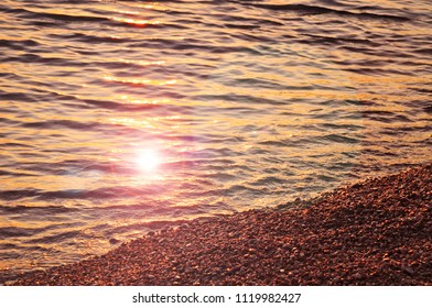 Beach and water at sunset sun rays