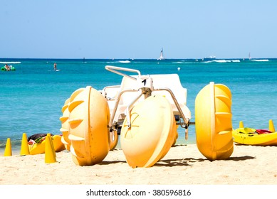 Beach water tricycles with huge yellow wheels on the beach of Honolulu.