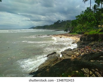 Beach waves crashing into rocks and decorating white sands and tree trees and green grass, this place is usually visited for a very enjoyable holiday and family fun event