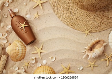 beach wear and accessories. summer hat, suntan lotion and seashells on sand beach background