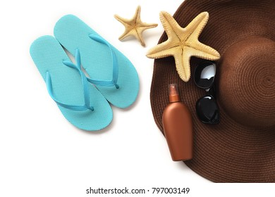 beach wear and accessories. summer hat, sandals, sunglasses, suntan lotion and seashells isolated on white background