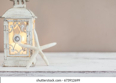 Beach wedding interior decor. Natural seashell and lantern on vintage shelf over pastel wall.