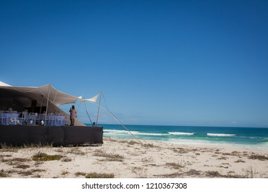 Beach wedding scene with a marquee