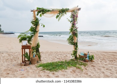 Beach wedding venue. Wedding on the beach . Wedding arch decorated of material and flowers on tropical sand beach. Wedding and honeymoon concept.