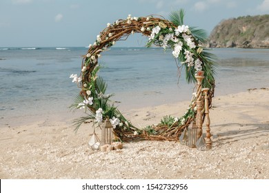 Beach wedding venue. Wedding on the beach . Round wedding arch decorated of material and flowers on tropical sand beach. Wedding and honeymoon concept