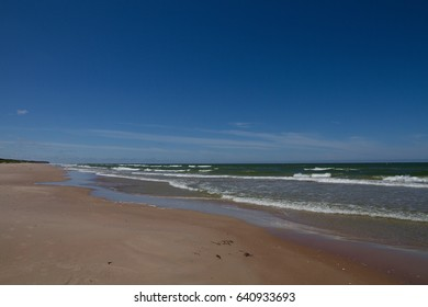 Beach with white sand and waves of Baltic Sea in a summer day with blue sky