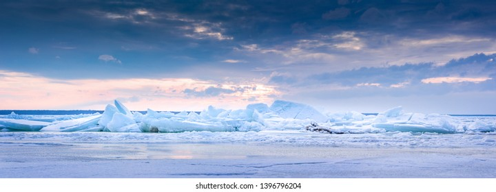 Beach in wintertime. Frozen sea, evening light and icy weather on shore like fairy tale country. Winter on coast. Blue sky, white snow, ice covers the land.