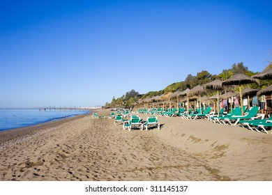 Beach witch sun loungers in Marbella, Spain, Costa del Sol, Andalucia region.
