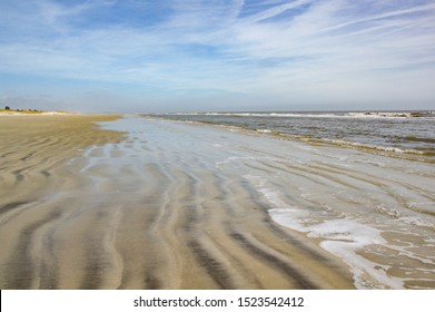 A beach without any people.  The gentle waves roll in on the rippled sand on Sapelo Island, SC.