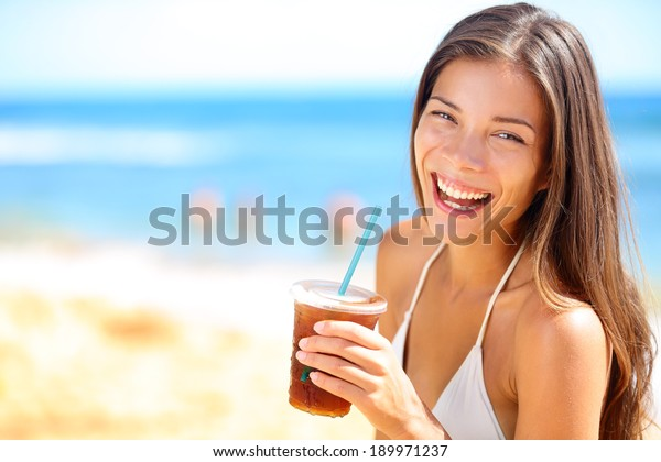 Beach woman drinking cold drink beverage having fun at beach party. Female babe in bikini enjoying Ice tea, coke or alcoholic drink smiling happy laughing looking at camera. Beautiful mixed race girl