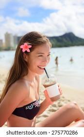 Beach woman drinking iced coffee cappuccino drink enjoying beach lifestyle smiling happy on Waikiki, Honolulu, Oahu, Hawaii, USA. Mixed race Asian Caucasian female in bikini.