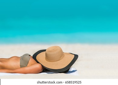 Beach woman sunbathing lying down sleeping covering her face with straw hat for uv sun rays protection on turquoise ocean background copyspace. Vacation girl relaxing tanning on summer travel.