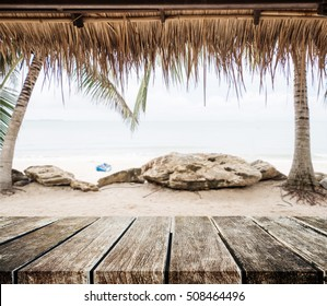 The beach, wooden tabletop with straw roof at tropical beach. Holiday beach travel