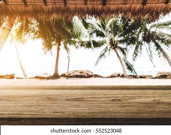 The beach, wooden tabletop with straw roof at tropical beach in sunrise