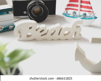 beach word on white background with Wooden Toy Sailboat, retro camera, wooden anchor, wooden Treasure Chest and map, travel on the beach concept