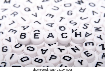 BEACH word written on blocks/dice with black letters top down mid shot in a puzzle of alphabets