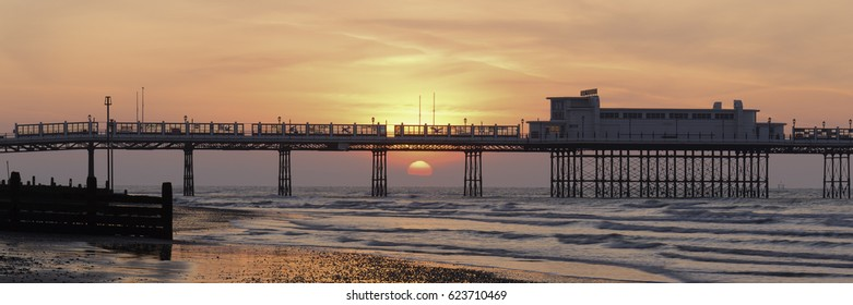 Beach at Worthing, England at sunrise with the sun low on the horizon and framed within the steel legs of the pier. Gentle waves lapping against the shore in the foreground.