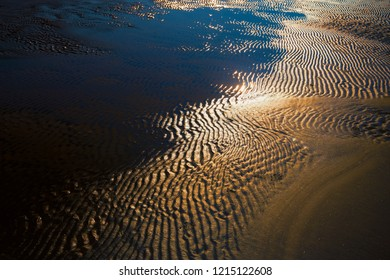 Beach of yellow sand with waves at low tide on a sunny day