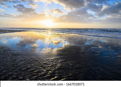 the beach in zandvoort during a great sunset with backlight and the north sea in the background