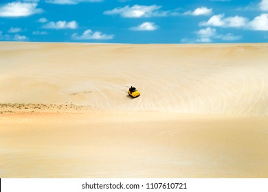 Beach-buggy with its tourist passengers races along the dunes at Genipabu near Natal, northeast Brazil