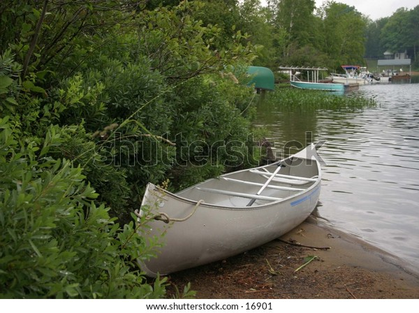 beached canoe  taken on lake surrounded by woods
