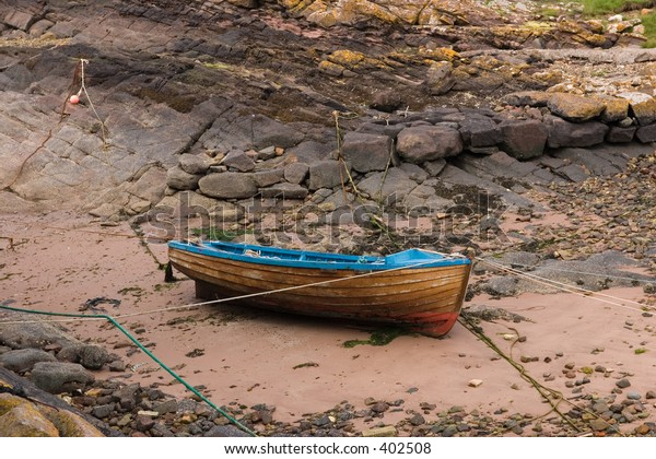 Beached rowing boat in tidal harbor