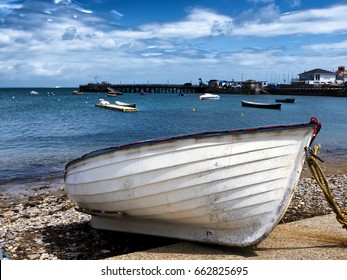 Beached rowing dinghy; white dinghy drawn up onto foreshore, against a beautiful ocean background