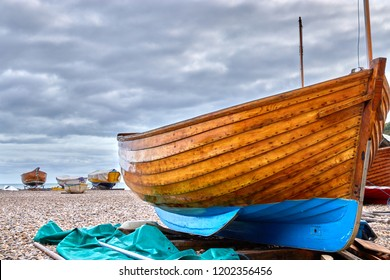 Beached wooden boat on Beer Beach in Devon, England with beached boats in the background and moody cloudy sky
