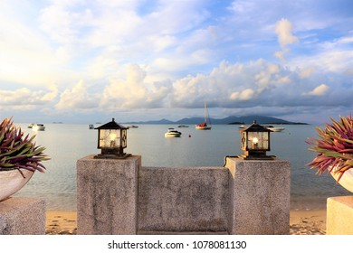 At the Beachfront patio seeing clear blue sky beautiful white clouds, floating yachts on the calm sea during sunset. A perfect orange sunlight shined to decorated lamps and plants