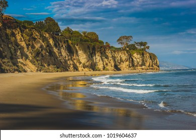 Beachside view of beautiful blue Pacific Ocean and stunning cliffs surrounding Dume Cove on a sunny day with clouds in the sky, Point Dume, Malibu, California