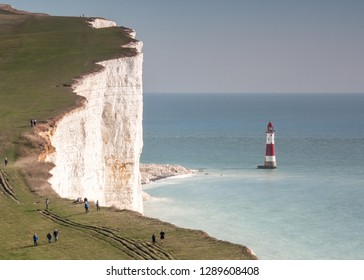 Beachy Head cliff and lighthouse. A view of the imposing chalk cliff face known as Beachy Head on the south coast of England dwarfing its lighthouse in the English channel.