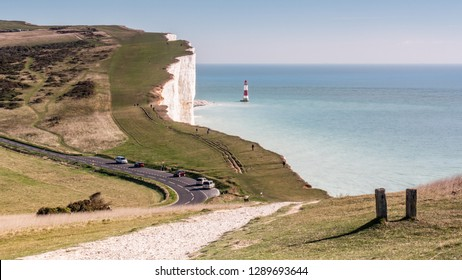 Beachy Head, the South Downs and the English Channel. A footpath leading into a view over the South Downs landscape on the south coast of England towards Beachy Head cliff and its lighthouse.