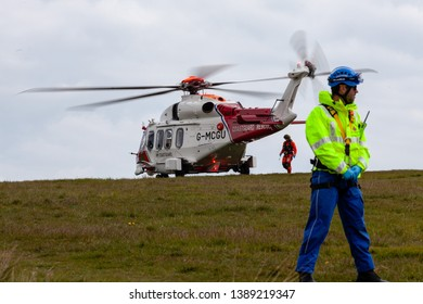 Beachy Head, Sussex, UK. 5th May 2019.  Pilot retruns to the coastguard helicopter after a body was retireved from the foot of the cliffs