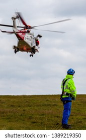 Beachy Head, Sussex, UK. 5th May 2019.  Coastguard helicopter searches the shoreline at Beachy Head